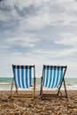 Two deck chairs on brighton beach england portrait shot of stripy blue and white a shingle in looking out to sea Royalty Free Stock Photography
