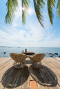 Two deck chairs on a wooden deck beautiful with table ashtray and menu facing the sea and palm leaves in sihanoukville cambodia Stock Image