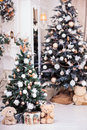 Two decorated Christmas tree with gift box near classical firepl