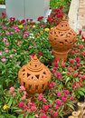 Two decorated clay pots in the flowers garden. Royalty Free Stock Photo