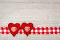Two decorated felt hearts side by side on a ribbon of red and white check material all on a gray grainy wooden surface Royalty Free Stock Photography
