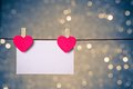 Two decorative red hearts with greeting card hanging on blue and golden light bokeh background, concept of valentine day Royalty Free Stock Photo