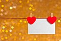 Two decorative red hearts with greeting card hanging on golden light bokeh background, concept of valentine day Royalty Free Stock Photo