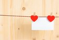 Two decorative red hearts with greeting card hanging on wood background, concept of valentine day Royalty Free Stock Photo