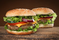 Two delicious hamburgers on wood background Stock Image