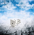 Two dice in motion, droughts desert , cloudy sky Royalty Free Stock Photo