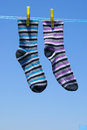 Two different socks hanging on the clothesline in the sun Stock Photos