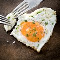 Two dinner forks pricking in a fried egg with heart shape Royalty Free Stock Photo