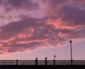 Two distant people walking on a bridge in the evening under sunset sky with orange purple clouds Royalty Free Stock Images