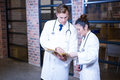 Two doctors looking at file and discussing near library in hospital Stock Image