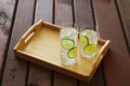 Two drinks on wooden tray with ice and condensation on glass Royalty Free Stock Photo