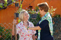Two elderly ladies chatting in the garden contented happy standing together sunshine Royalty Free Stock Photo