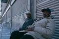 Two elderly men sat outside of closed shops, Manhattan, New York, USA Royalty Free Stock Image