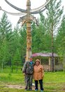 Two elderly Yakuts a man and a woman stand hugging and smiling under the national ritual pillar of Serge