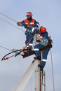 Two electrics working on top of an electricity pylon electrician with the use ladder and belt Stock Photo