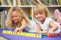 Two elementary pupils counting together in classroom lying down having fun Royalty Free Stock Photo