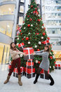 Two employees of the bank with a gift moscow dec in hands standing next to large christmas tree in main office rosbank on Royalty Free Stock Photography