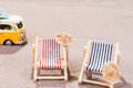 Two empty beach chairs in the sand, with old van Royalty Free Stock Photo