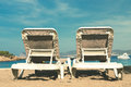 Two empty deckchairs on a sandy beach facing the ocean blue skies and a small speed boat Royalty Free Stock Images