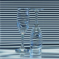 Two empty glasses with bands of refraction blinds in the background and blue backlight Royalty Free Stock Photo
