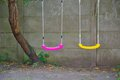 Two empty swings in purple and yellow Royalty Free Stock Photo