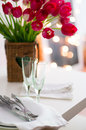 Two empty wine glasses on a table and bouquet of flowers in daylight Stock Photos