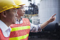 Two engineers in protective workwear pointing outside of a factory Stock Image