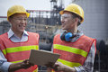 Two engineers in protective workwear standing and laughing outside of a factory Royalty Free Stock Photos
