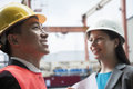 Two engineers smiling in protective workwear outside in a shipping yard Stock Images