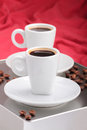 Two espresso cups on a gray metallic table on red background blur Stock Photography