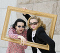 Two European young beautiful business womans in dark glasses in a picture frame . Royalty Free Stock Photo
