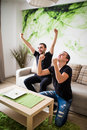Two excited friends or roommates watching tv on line sitting on a couch in the living room at home Royalty Free Stock Photo