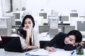 Two exhausted businesswoman with a laptop on the desk in office Royalty Free Stock Photography