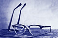 Two eyeglasses on the table with blue background Royalty Free Stock Photos