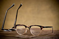 Two eyeglasses on the table with brown background Royalty Free Stock Photos