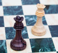 Two faced queens wooden chess pieces on chessboard Royalty Free Stock Photo