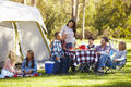 Two families enjoying camping holiday in countryside sitting down having a picnic Royalty Free Stock Photography