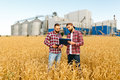 Two farmers stand in a wheat field with tablet. Agronomists discuss harvest and crops among ears of wheat with grain Royalty Free Stock Photo