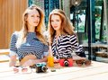 Two fashion beautiful girls sitting in a summer cafe. On the table is beautiful vintage camera and orange beverage a straw from a Royalty Free Stock Photo