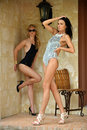 Two fashion models in designers swimsuit posing front of house Stock Image