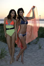 Two fashion models posing on the beach dunes wearing sexy swimsuits on sunset time with effective background of sky and verrazano Royalty Free Stock Image