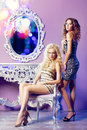 Two fashion models posing in glamorous interior interiors Royalty Free Stock Photos