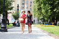 Two fashion women walking in the summer city Royalty Free Stock Photo