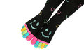 Two feet in happy socks with toes black colorful smileys the are colorful smileys too are arranged diagonal isolated Royalty Free Stock Photography
