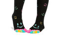 Two feet in happy socks with toes black colorful smileys the are colorful smileys too the person is standing on the deck Stock Images