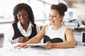 Two female architects working together at a desk in office Royalty Free Stock Photo