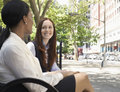 Two female colleagues talking on street multiethnic Stock Photos