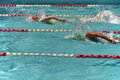 Two female freestyle swimmers in a close race during an outdoor swim meet Stock Photos