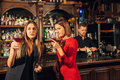Two female friends are in the bar for a drink and talk. The woman with talks near the ear of the friend Royalty Free Stock Photo
