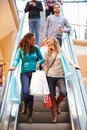 Two female friends on escalator in shopping mall having a conversation Royalty Free Stock Image
